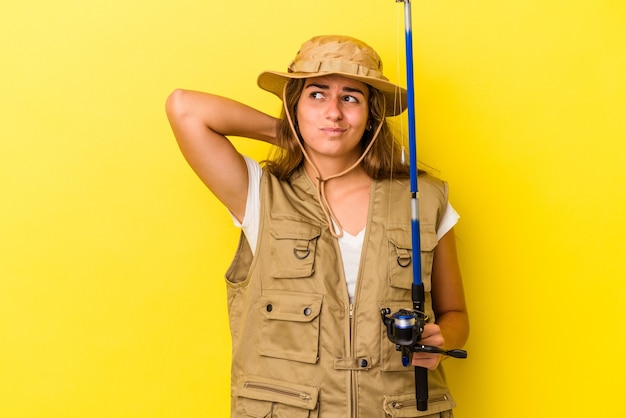 머리 뒤쪽을 만지고 생각하고 선택하는 노란색 배경에 고립 된 막대를 들고 젊은 백인 어부.
