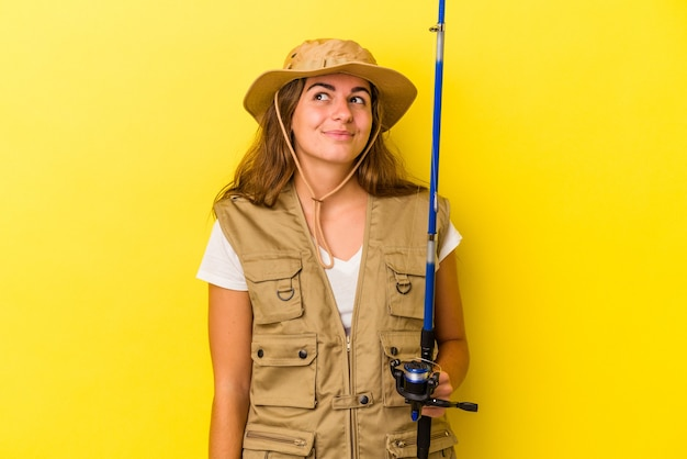 Young caucasian fisherwoman holding a rod isolated on yellow background  dreaming of achieving goals and purposes Premium Photo