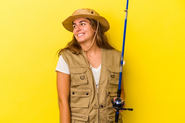 Young caucasian fisherwoman holding a rod isolated on yellow background  looks aside smiling, cheerful and pleasant.