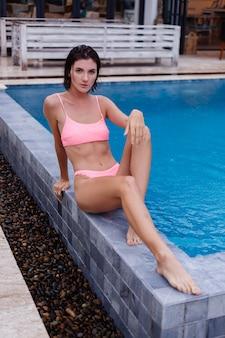 Giovane donna caucasica abbronzata in forma sottile in bikini rosa brillante fuori dalla villa