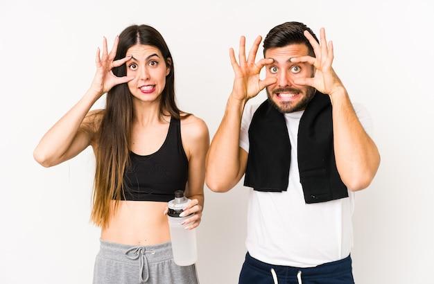 Молодые кавказские пары фитнеса изолировали держа глаза открытыми, чтобы найти возможность успеха.
