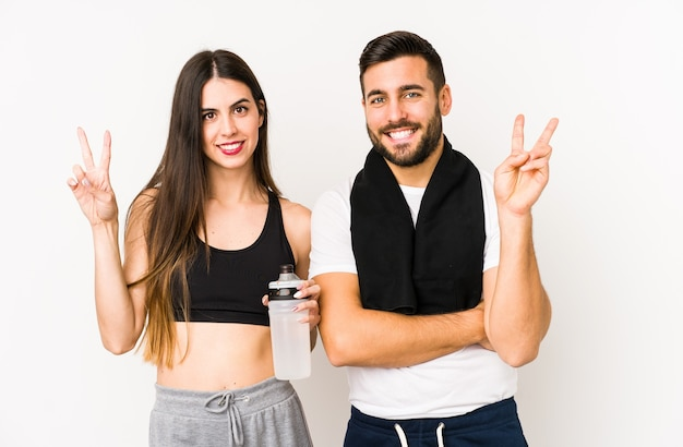 若い白人のフィットネスカップルは、指で2番目を示して分離しました。