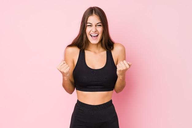 Молодая кавказская женщина фитнеса, занимающаяся спортом, изолировала аплодисменты, беззаботно и взволнованно. концепция победы.