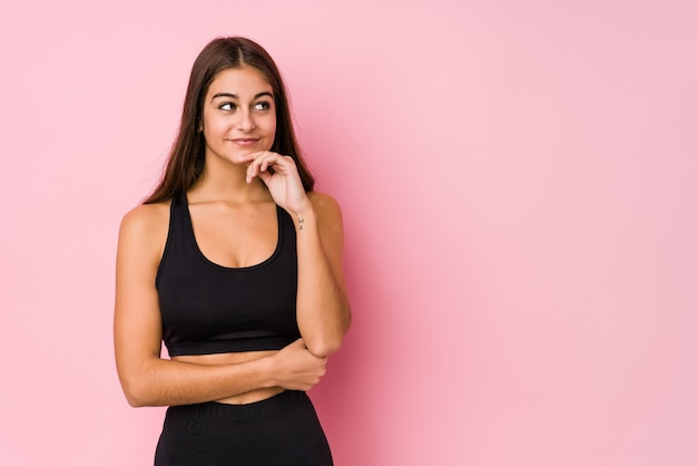 Young caucasian fitness woman doing sport isolated looking sideways with doubtful and skeptical expression.