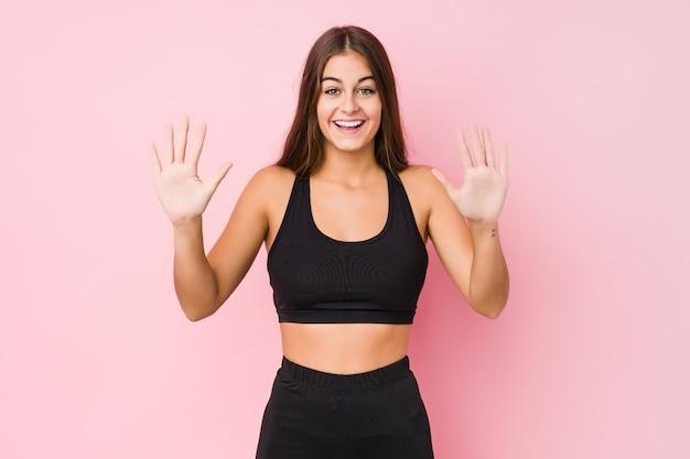 スポーツをしている若い白人フィットネス女性は手で数10を示します。
