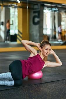 운동복을 입은 젊은 백인 피트니스 여성은 체육관에서 요가 매트에 누워 복근 운동을 하고 피트니스 공을 사용합니다. 스포츠, 운동, 웰빙 및 건강한 라이프 스타일