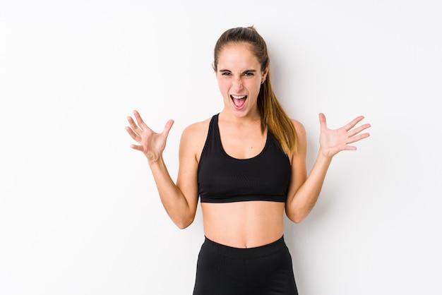 Молодая кавказская женщина фитнеса представляя в белой стене кричащей с яростью.