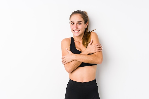 Young caucasian fitness woman posing in a white going cold due to low temperature or a sickness.