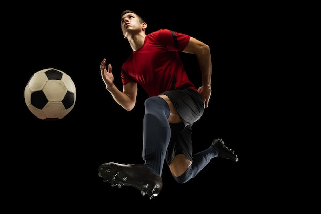 Young caucasian football, soccer player in action, motion isolated on black background