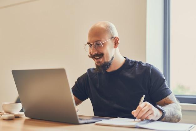 Молодой кавказский фрилансер работает с ноутбуком за своим столом в офисе, делая что-то заметки