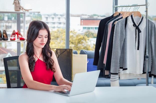 젊은 백인 친절 한 여자 노트북 작업 및 옷이 게에서 온라인 전자 상거래 쇼핑 판매.