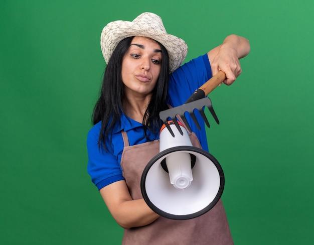 コピースペースと緑の壁に分離されたスピーカーを見て熊手とスピーカーに触れる制服と帽子を身に着けている若い白人の庭師の女の子