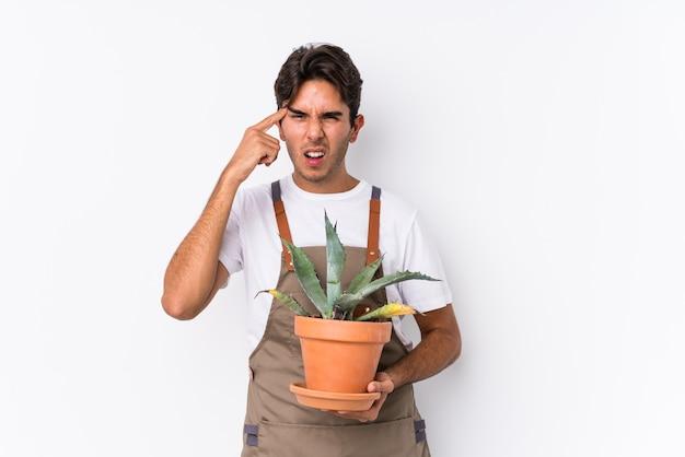 人差し指で失望のジェスチャーを示す孤立した植物を保持している若い白人の庭師の男。