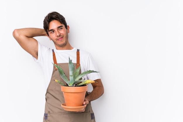 頭の後ろに触れて、考えて、選択をする孤立した植物を持っている若い白人の庭師の男。