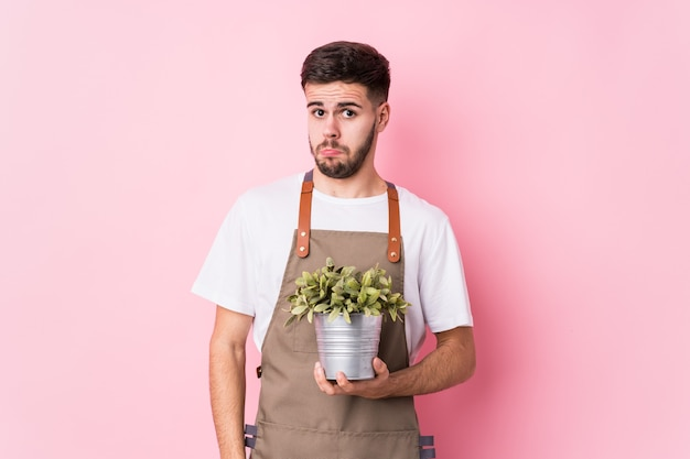 Young caucasian gardener man holding a plant isolated shrugs shoulders and open eyes confused.