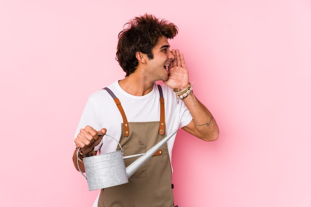 Young caucasian gardener man isolated shouting and holding palm near opened mouth.