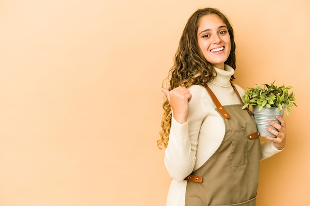 植物を持っている若い白人の庭師の女性は、親指の指を離れて、笑って、のんきなポイントを分離しました。
