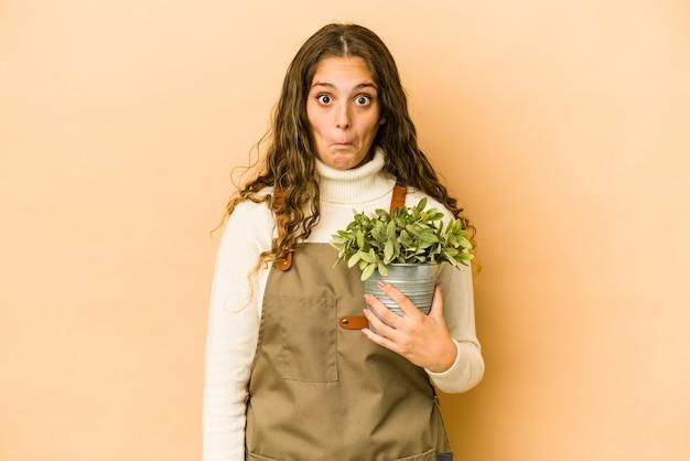 植物を保持している若い白人の庭師の女性は、肩をすくめ、目を開けて混乱しました。