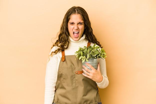 매우 화가 공격적 비명 식물을 들고 젊은 백인 정원사 여자.