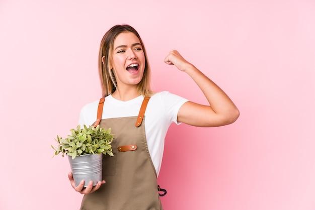 Молодая кавказская женщина садовника на розовом кулаке подъема после победы, концепции победителя.