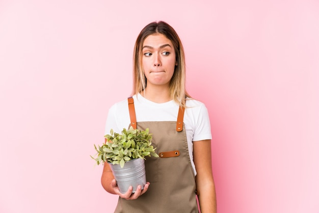 Young caucasian gardener woman in pink confused, feels doubtful and unsure.