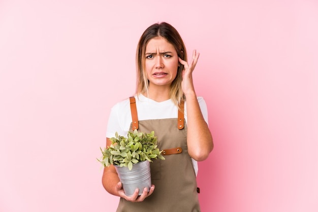 Young caucasian gardener woman in a pink wall covering ears with hands.