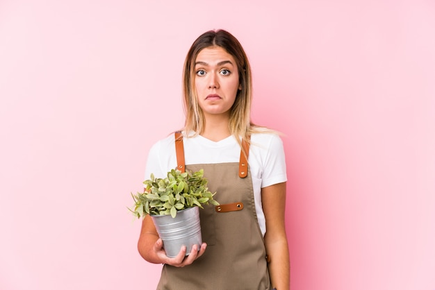 Young caucasian gardener woman in a pink wall shrugs shoulders and open eyes confused.