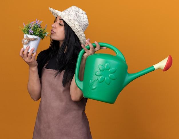 Giovane donna caucasica del giardiniere che indossa uniforme e cappello che tiene vaso di fiori e annaffiatoio che annusa fiori
