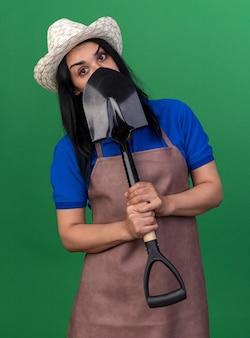 Giovane donna caucasica del giardiniere che indossa l'uniforme e il cappello che tiene la vanga da dietro