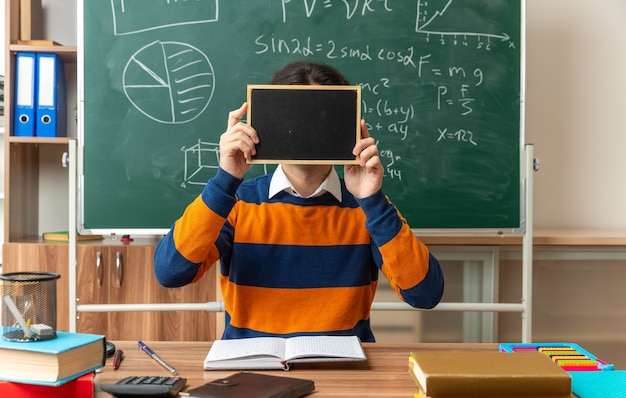 顔の前にミニ黒板を保持している教室で学校の道具と机に座って眼鏡をかけている若い白人幾何学教師