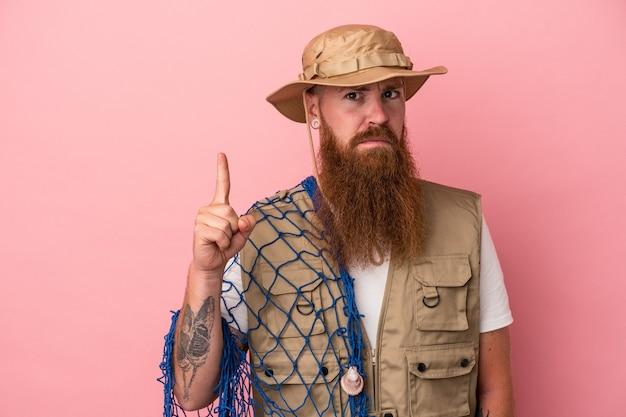 ピンクの背景で隔離のネットを保持している長いひげを持つ若い白人生姜漁師