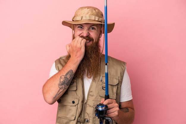 Молодой кавказский рыбак имбиря с длинной бородой, держащий удочку, изолированную на розовом фоне, кусает ногти, нервничает и очень тревожится.