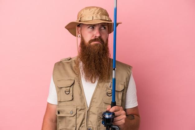 Молодой кавказский рыбак имбиря с длинной бородой, держащий удочку, изолированную на розовом фоне, смущен, чувствует себя сомнительным и неуверенным.