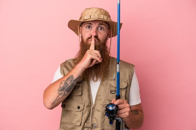秘密を保持するか、沈黙を求めてピンクの背景に分離されたロッドを保持している長いひげを持つ若い白人生姜漁師。