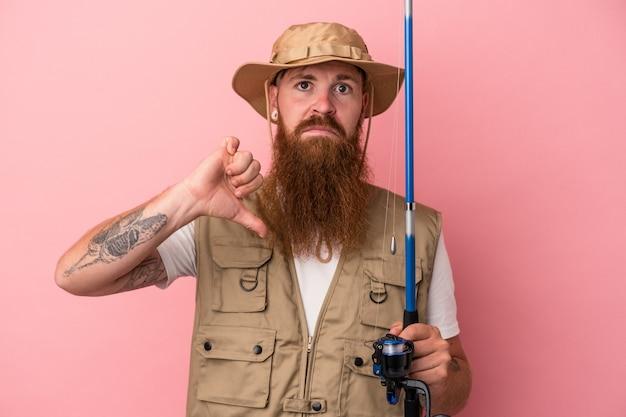 ピンクの背景に分離されたロッドを保持している長いひげを持つ若い白人の生姜漁師は、嫌いなジェスチャーを示し、親指を下に向けます。不一致の概念。