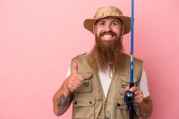 Молодой кавказский имбирный рыбак с длинной бородой, держащий удочку на розовом фоне, улыбается и поднимает большой палец вверх