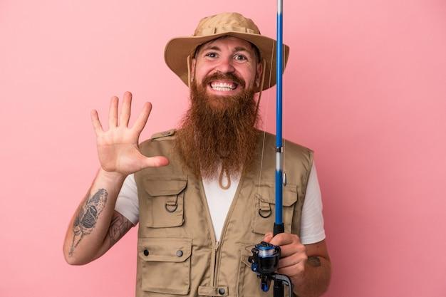 Молодой кавказский рыбак имбиря с длинной бородой, держащей удочку, изолированную на розовом фоне, улыбается веселый, показывая номер пять с пальцами.