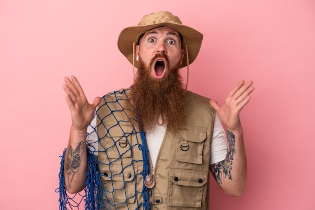 Young caucasian ginger fisherman with long beard holding a net isolated on pink background