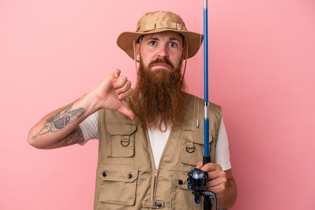 Young caucasian ginger fisherman with long beard holding a rod isolated on pink background showing a dislike gesture, thumbs down. disagreement concept.