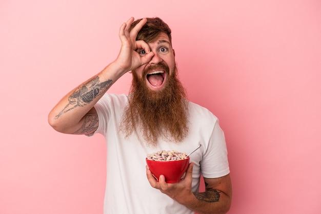 ピンクの背景に分離されたシリアルのボウルを保持している長いひげを持つ若い白人の生姜男は、目に大丈夫なジェスチャーを維持して興奮しました。