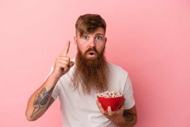 アイデア、インスピレーションのコンセプトを持つピンクの背景に分離されたシリアルのボウルを保持している長いひげを持つ若い白人生姜男。