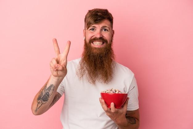 ピンクの背景に分離されたシリアルのボウルを保持している長いひげを持つ若い白人の生姜男は、指で2番目を示しています。