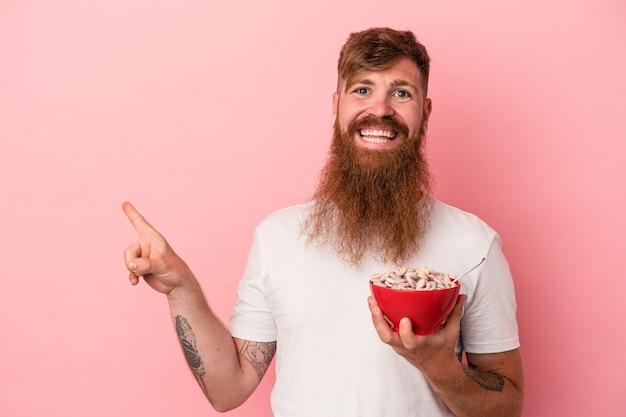 ピンクの背景に分離されたシリアルのボウルを保持している長いひげを持つ若い白人の生姜男は、笑顔で脇を指して、空白のスペースで何かを示しています。