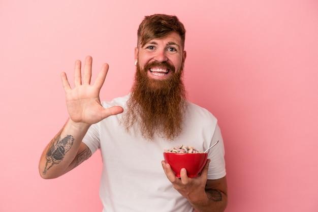 ピンクの背景に分離されたシリアルのボウルを保持している長いひげを持つ若い白人の生姜男は、指で5番を示して陽気に笑っています。