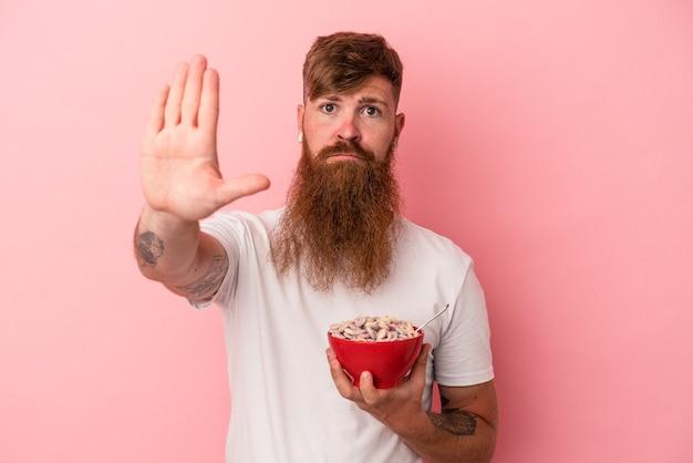 ピンクの背景に分離されたシリアルのボウルを保持している長いひげを持つ若い白人の生姜男は、一時停止の標識を示している手を伸ばして立って、あなたを防ぎます。