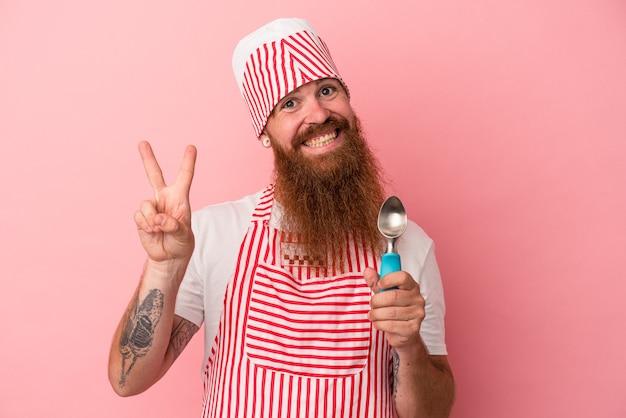 ピンクの背景に分離されたスクープを保持している長いひげを持つ若い白人の生姜男は、指で平和のシンボルを喜んで気楽に示しています。
