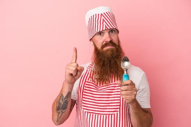 ピンクの背景に分離されたスクープを保持している長いひげを持つ若い白人の生姜男は、指でナンバーワンを示しています。