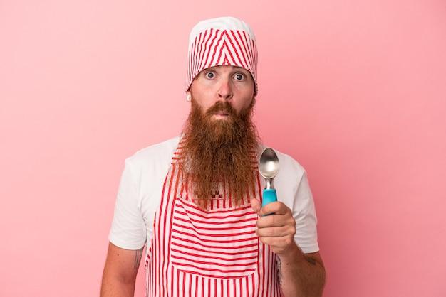 ピンクの背景に分離されたスクープを保持している長いひげを持つ若い白人の生姜男は肩をすくめ、目を開いて混乱します。