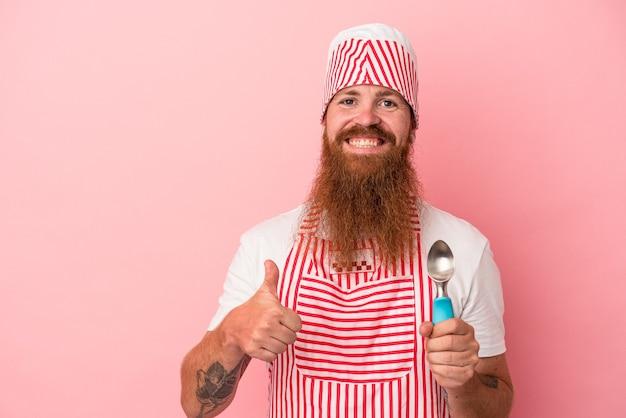 ピンクの背景に分離されたスクープを持って笑顔で親指を上げて長いひげを持つ若い白人生姜男