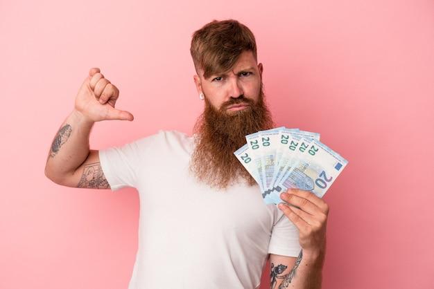 Молодой кавказский рыжий мужчина с длинной бородой, держащий банкноты на розовом фоне, чувствует себя гордым и уверенным в себе, пример для подражания.